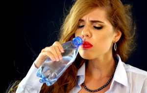 woman frowning from drinking cold water