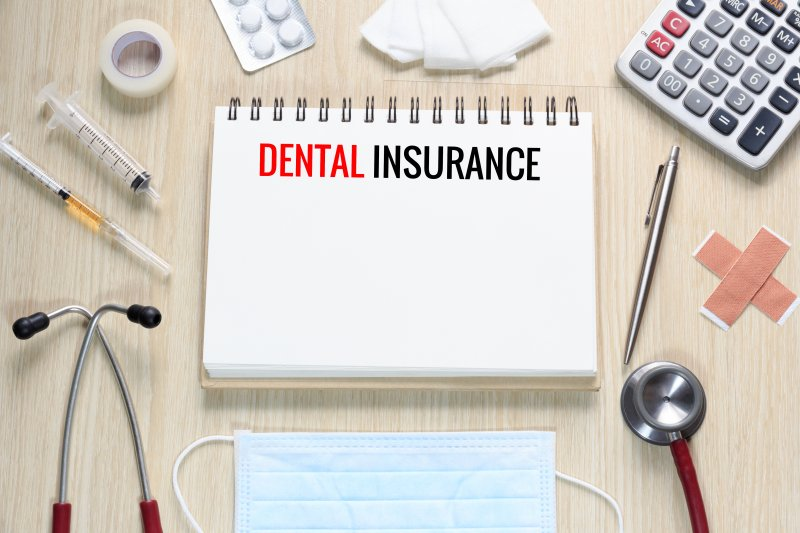 """Notepad reading """"Dental Insurance"""" surrounded by medical equipment"""